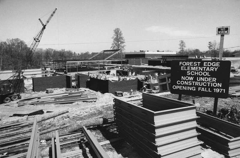 Black and white photograph of the construction of Forest Edge Elementary School. In the foreground, there is a sign announcing the name of the school and that it will be opening in fall of 1971. Workmen can be seen performing various tasks. In the background, there are trees without foliage.