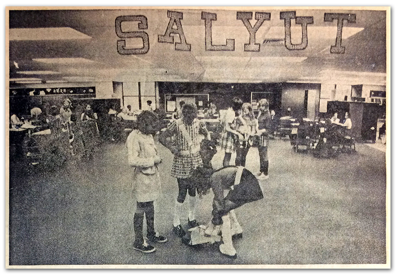 Black and white photograph of Salyut Crater that appeared in the Sun Newspaper. The clipping does not show the newspaper's printing date, but it was likely between 1971 and 1973 because no classroom partitions are visible in the photograph. The first partitions to the learning area were added in 1973. Three safety patrol students can be seen in the foreground putting on their belts. In the background students are clustered around groups of tables.