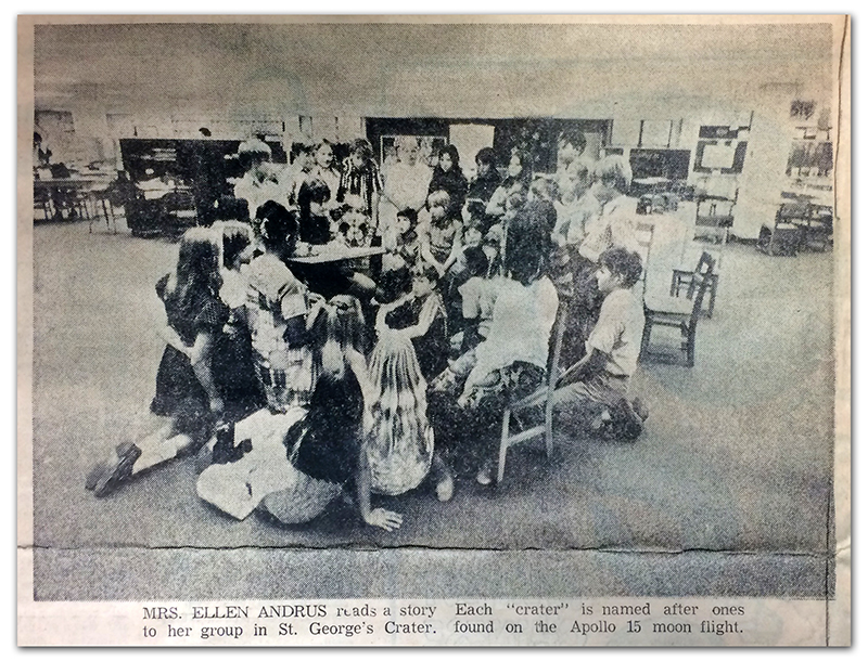 Black and white photograph of St. George's Crater that appeared in the Sun Newspaper. The clipping does not show the newspaper's printing date, but it was likely between 1971 and 1973 because no classroom partitions are visible in the photograph. A group of approximately 30 students are clustered around a table in the center of the crater where the teacher is reading a story. The image caption reads: Mrs. Ellen Andrus reads a story to her group in St. George's Crater. Each crater was named after ones found on the moon by the crew of NASA's Apollo 15 spaceflight.