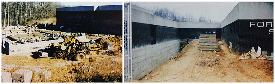 Two color photographs, side-by-side, of the building renovation during the early 2000s. Both show the outside of the building. In the photograph on the left, an area that was once a basketball court has been ripped up and a new wing of the building is being constructed. The cinderblock walls are starting to go up and a backhoe is working the foreground. In the photograph on the right, the sidewalk that led between the original two main wings of the building has been ripped up. The ground has been excavated along the foundation. This section will be enclosed during the renovation and will become part of the new library.