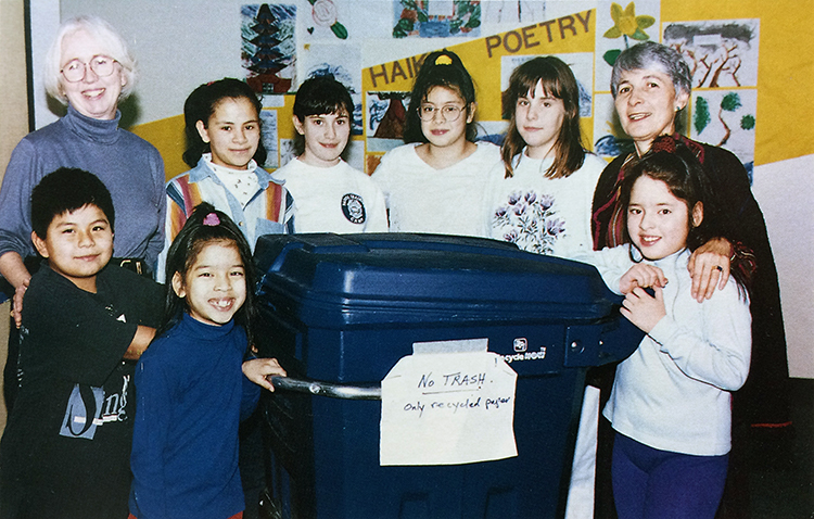 Color photograph of the Earthsavers Club from the 1996 Forest Edge yearbook. Seven students and two sponsors are standing around a large, blue recycling bin. A sign on the bin reads: No Trash! Only recycled paper.