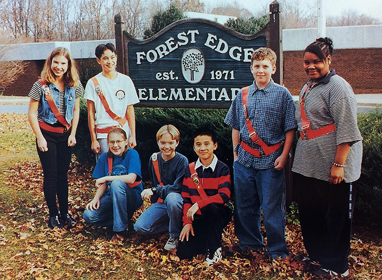 Color yearbook photograph of students who served in the Forest Edge Safety Patrol. Seven students, wearing bright orange belts, are pictured. Some are standing, some kneeling, around the sign in front of our school. The sign reads: Forest Edge Elementary, established 1971. The sign is made out of wood and is painted brown and dark green with white lettering. An emblem of a tree is in the center.